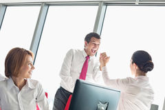 Businesspeople celebrating success in office Stock Photos