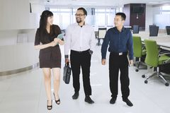 Businesspeople chatting while walking in office.  Stock Photography
