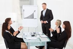 Businesspeople clapping for colleague after presentation Royalty Free Stock Photos