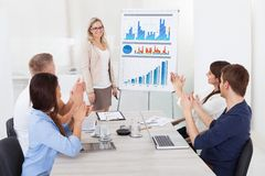 Businesspeople clapping for female colleague after presentation. Young businesspeople clapping for female colleague after presentation at desk in office Stock Image