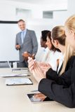 Businesspeople clapping for a man in meeting Royalty Free Stock Photos