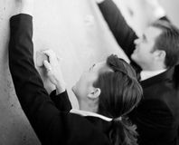 Businesspeople Climb. Three businesspeople in suits climbing wall to reach top royalty free stock photos