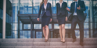 Businesspeople climbing down steps stock images