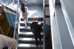 Businesspeople climbing staircase in office Stock Photo