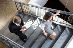 Businesspeople climbing staircase in office Royalty Free Stock Image