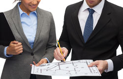 Businesspeople with clipboard, blueprint, helmet Stock Images
