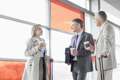 Businesspeople with coffee cups talking on railroad platform Royalty Free Stock Photography