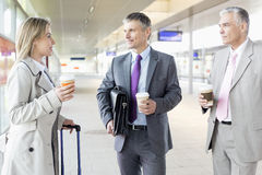Businesspeople with coffee cups talking at railroad platform Stock Photos