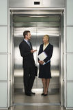 Businesspeople Communicating In Elevator. Happy business colleagues communicating in elevator stock images