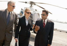 Businesspeople communicating with helicopter in background Stock Photography