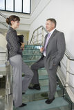 Businesspeople Communicating On Staircase In Office Royalty Free Stock Photography