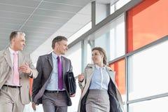 Businesspeople communicating while walking on railroad platform Stock Photo