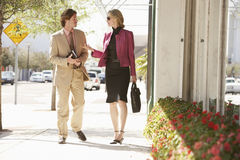 Businesspeople Communicating While Walking On Sidewalk. Businessman and businesswoman communicating while walking on sidewalk stock images