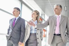 Businesspeople communicating while walking on train platform Stock Images