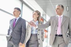 Businesspeople communicating while walking on train platform Stock Images