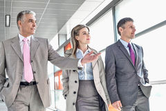 Businesspeople communicating while walking on train platform Royalty Free Stock Image