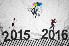 Businesspeople compete above numbers 2016. Three businesspeople compete to get success by jumping and running above numbers 2015 to 2016 Royalty Free Stock Photo