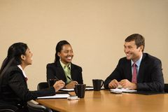 Businesspeople in conference. Businesspeople sitting at conference table talking and smiling royalty free stock photography