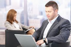 Businesspeople during conference break. Businesspeople sitting in hallway during conference break royalty free stock image