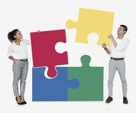 Businesspeople connecting jigsaw puzzle pieces stock photography