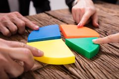 Businesspeople Connecting Pieces Of Pie Chart. Businesspeople Connecting Pieces Of Multi Colored Pie Chart On Wooden Desk stock photos