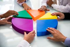 Businesspeople Connecting Pieces Of Pie Chart. Businesspeople Hand Connecting Multi Colored Pieces Of Pie Chart On Desk stock images