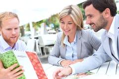 Businesspeople deciding menu at sidewalk cafe Stock Image