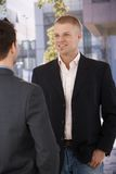 Businesspeople die bij de bureaubouw spreekt Stock Fotografie