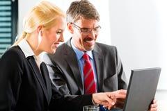 Businesspeople die laptop in overleg bekijken royalty-vrije stock afbeelding