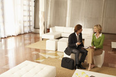 Businesspeople Discussing In Office Lobby. Businessman and businesswoman discussing in office lobby Royalty Free Stock Images