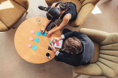Businesspeople discussing over adhesive notes in office lobby. Top view of businessman and businesswoman discussing over adhesive notes on table in office lobby stock photos