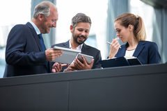 Businesspeople discussing over digital tablet Stock Image