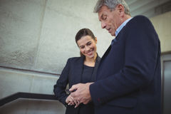 Businesspeople discussing over electronic device in corridor. At office stock photo