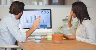 Businesspeople discussing over graphic chart on computer. In office Stock Photos