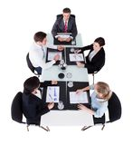 Businesspeople Discussing Over Graphs At Conference Table. High angle view of businesspeople discussing over graphs at conference table against white background royalty free stock photography