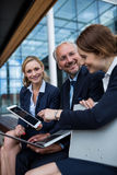 Businesspeople discussing over laptop and digital tablet Royalty Free Stock Photography