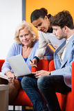 Businesspeople Discussing Over Laptop In Lobby Royalty Free Stock Images