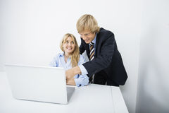 Businesspeople discussing over laptop in office Stock Image