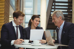 Businesspeople discussing over a paper document Stock Image