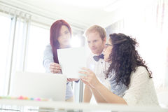 Businesspeople discussing over photograph in creative office Royalty Free Stock Photos