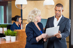 Businesspeople Discussing On Paperwork At Office Stock Photos