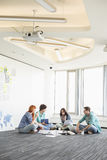 Businesspeople discussing while sitting on floor in creative office Stock Photography