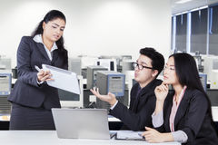 Businesspeople discussing something with tablet. Multi ethnic business team using digital tablet to discuss business project in the office Royalty Free Stock Image