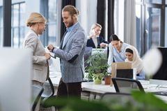 Businesspeople discussing work in office. Selective focus of businesspeople discussing work together in office stock photography