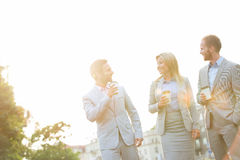 Businesspeople with disposable cups conversing against clear sky on sunny day Royalty Free Stock Photography