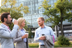 Businesspeople with disposable cups conversing in city Royalty Free Stock Images