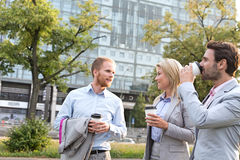 Businesspeople with disposable cups conversing in city Stock Photos