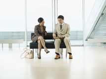 Businesspeople With Documents At Airport Lobby. Businesspeople looking over documents on bench in the airport royalty free stock images