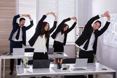 Businesspeople Doing Exercise Behind Desk. Happy Businesspeople Doing Stretching Exercise Behind Desk At Workplace royalty free stock image