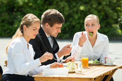 Businesspeople Eating Food In Restaurant. Young Happy Male And Female Businesspeople Eating Food In Restaurant Stock Photos